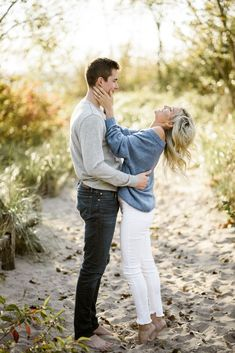 Blonde in blue sweater and man in grey sweater on the beach. Great photo idea for your engagement shoot. Gotta love sweaters! Photographed by Alix Gould.