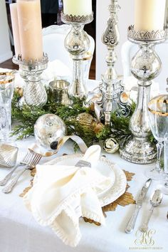 Christmas dining room. Elegant white and gold with evergreens. place setting