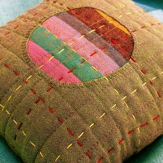 Pincushion - Stitched, Patched and Quilted by Victoria Gertenbach    Inspired by Japanese Boro textiles.  Featuring shot cottons, machine and hand quilting.    little work of art!