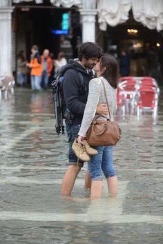 """Una pareja descalza se da un beso en una plaza de San Marcos inundada durante el primer """"acqua alta"""" de la temporada en Venecia. El """"acqua alta"""" es una convergencia de las mareas altas y un fuerte siroco, alcanzando los 105 centímetros. AFP PHOTO / Pattaro ANDREA."""