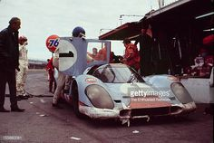 Jo Siffert Brian Redman of JW Engineering stand in the pits with their Gulf Porsche 917 K