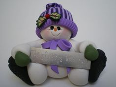 Polymer clay roly poly snow lady.  Holding a sign that reads, The stockings were hung.  Purple striped hat  Holly accents  Measures 1 3/4 tall and