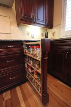 Keep your spices in a row by organizing them in a seamless pull out column! #organization #cabinetry
