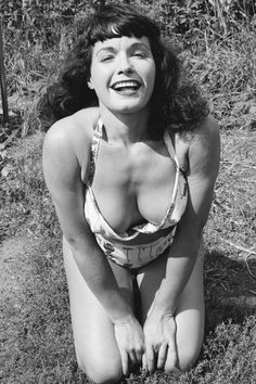 """BETTIE PAGE, 1956. The """"Queen of Pinups"""" boasted enviable curves (36-23-35, to be exact), but it's her cropped bangs that left a lasting beauty impression."""