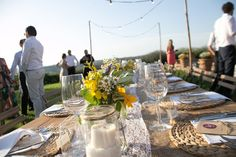 Country wedding in Tuscany, wildflowers and sunflowers bouquets in masojars decorated with lace, burlap and twine as table decorations