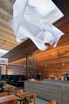 luminous & undulating glass drapery sculpture (by Nikolas Weinstein) reflects light from the skylights it encompasses  . Bar Agricole, San Francisco . Aidlin Darling Design