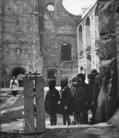 1944 London at War - St. Clement Danes church    London 1944 - Children waiting to collect oranges and a few lemons from crate at bombed out St. Clement Danes church.