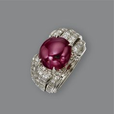 RUBY AND DIAMOND RING, CIRCA 1935 Set with an oval cabochon ruby weighing approximately 7.50 carats, flanked by rows of 48 single-cut and 16 round diamonds weighing approximately 1.10 carats, mounted in platinum, size 3½, numbered 3055.
