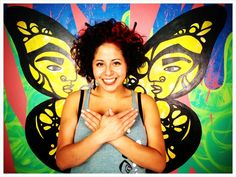 """Image] Social justice digital artist, Faviana Rodriguez standing in front of her monarch butterfly mural, smiling and signing butterfly; """"The monarch butterfly has come to represent the beauty of migration. Adopted by various migrant rights organizations, artists, and lovers of justice, the butterfly symbolizes the right that living beings have to freely move. Like the monarch butterfly, human beings cross borders in search of safer habitats...in order to survive."""