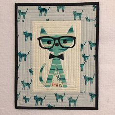 "Pam Sizemore / uberstitch on flickr says: ""The mini I sent my partner in the ""cat"" themed miniquilt swap.  I miniaturized from a free quilt pattern ""hipster Cat"" by shwinpics"""