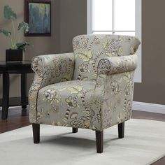 Add extra seating to your living room with an upholstered armchair. This chair features a muted floral print that will complement a variety of neutral sofas. The decorative welt cord and solid wood legs are two elegant details that enhance this piece.