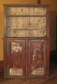 """18th C. Painted Cupboard - Very early and primitive pewter cupboard in old paint. Great form and paint. Chamfered doors. Beaded face frame. Several layers of paint as shown. Missing top doors. Damage to back. Other minor damage consistent with age.  Measures 46"""" wide x 17"""" deep x 70 1/2"""" tall"""