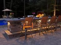 Cast Veneer Stone walls with key lighting creates a unique look for this poolside kitchen/bar design.  www.ephenry.com