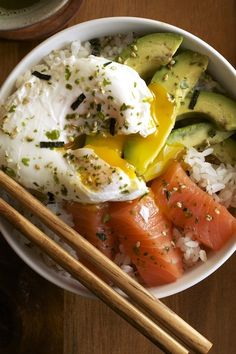 salmon sashimi, creamy avocade, poached egg on rice.  sprinkle with furikake. http://rachaelwhite.me/salmon-sashimi-rice-bowl/ Oh my goodness that looks absolutely divine! <3 :3