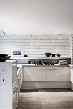 White brick modern accent with track lighting.