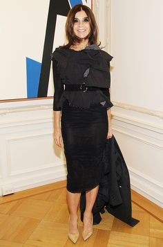Carine Roitfeld wearing a black pencil skirt and belted top with pointed-toe heels