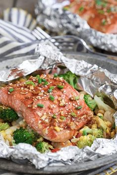 Sriracha honey salmon vegetable packets. 15 Foil-Packet Dinner Recipes that Make Cleanup a Breeze #purewow #dinner #grilling #easy #food #recipe #cooking #foilpacketrecipes #foilpackets #campingrecipes #sriracha #honeysalmon