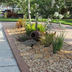 Landscape ideas -- love the use of rocks and large flat stone with grass. Easy care and beautiful.