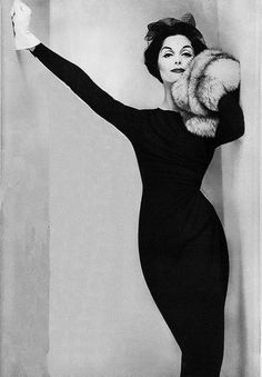 Dovima 1954 - Photo by Irving Penn - right arm lifted from the shoulder and extended to lean on right wall. left hip is leaning on left wall. left arm is also leaning against left wall but is raised at shoulder with elbow bent, left hand appears to be on shoulder. Left leg is in front of right leg