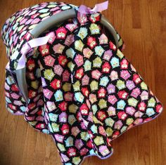 Handmade infant car seat canopy/cover  in  black with owl print fabric. Cotton  with contrasting purple polka dot piping / fleece lining.