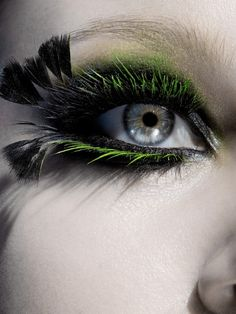 This eye makeup is very bold, in regards to the color green boldly contrasting the black, as well as the very long feather lashes