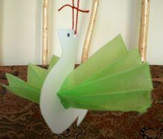 """bird in flight"": swan shape cut out of cardstock with hole in body to stick ""fan-folded"" tissue paper through for wings"