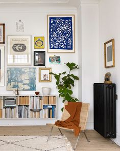 Paint the radiator black to act as art/focal point. Gorgeous gallery wall and wall mounted bookshelf. Greenery and corner easy chair.