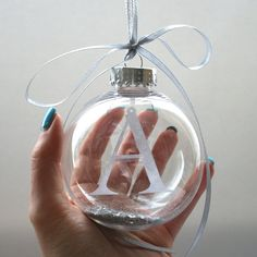 Personalised Papercut Initial Bauble by StudioCharley on Etsy These gorgeous acrylic glass baubles contain a personalised initial papercut, hand cut from 100 gsm matt white cartridge paper, hanging from an invisible thread. Each bauble is also then partially filled with loose chunky silver glitter, and hung on two strands of ribbon that end in a beautiful bow.