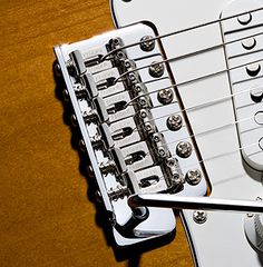 Modern Stratocaster® bridge (above) and vintage-style Precision Bass® bridge (below). In each, the long spring-surrounded screws that run in line with the strings through each individual bridge saddle from the back of the bridge plate enable fine intonation adjustments with relative ease.