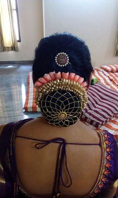 What a beautiful large low bun with decorative flowers and juda net! Care however should be taken before adopting such hairstyles, as due to it's high static charge, it will cause phlegm to move up in the throat, causing the voice to quaver & a frequent urge to clear the throat. A heavy chabi chhalla with a long & wide hook if inserted at the edge of the pleats of the saree, will reduce this problem as it's hook will activate the acupressure points that act to keep the throat clear.