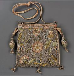 Drawstring bag. Late 16th early 17th century. 13x13cm. Linen plain weave embroidered with silk, sliver and gold metallic threads.  Braded silk and metallic cords and tassels