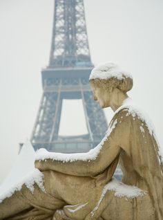 Pensive statue on a snowy Paris day.