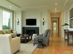 Living space with defined ceiling treatments, curved exterior wall, and contrasted fireplace.