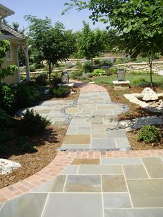 Bluestone patio and walkways, edged with brick and Mexican beach pebbles. #TopekaLandscape