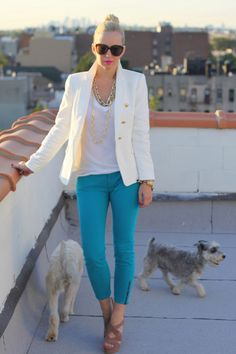turquoise pants, fresh white top, and gold necklace.