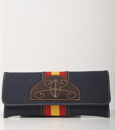 Cartera de mano hecha en tela y piel, tiene en el centro una aplicacion recordando a los zahones andaluces y la bandera de España. Cierre de botón con imán e interior con forro textil y bolsillo. Disponible en tres colores.Producto 100% español.  Medidas: 26 x 12 x 2 cm