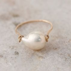 "Display an iridescent baroque pearl on this simply elegant ring, hand-crafted by Brooklyn-based designer Mary MacGill.- White baroque pearl, 14k gold fill hammered wire- Clean with warm water and soft cloth- Stone: 0.5""W, 0.5""L- Handmade in the USASize 7"