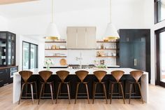 Stunning kitchen with high ceilings, large white and gold pendant lights, brown barstools, and white countertops