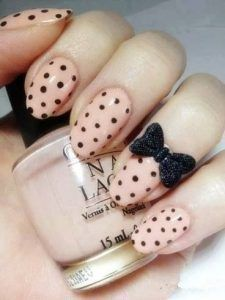 Black dots on nails with nude shade and a bow embellishment looks so elegant