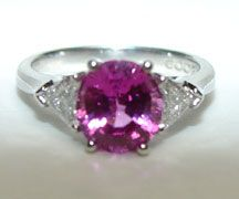 Fine pink Burma Sapphire oval shaped center stone with trillion accent side diamonds in platinum traditional three stone ring mounting.