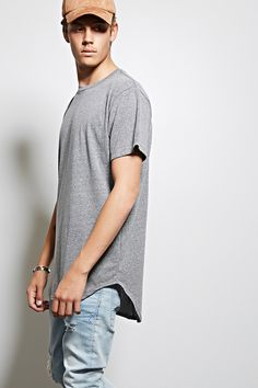 A soft heathered knit longline tee by MNML™ featuring a curved high-low hem, short sleeves, rear center seam construction, and a crew neck.