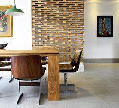 Na reforma deste apartamento, a arquiteta Gabriela Marques integrou ambientes e a sala avançou no espaço da cozinha. Com a criação de um painel ela escondeu a porta. As peças de madeira funcionam como elementos vazados, que não barram a luz