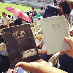 A dear brother holding his new revised NWT in Korean on the day of its release at the international convention in Seoul, along with the Bible that he used to maintain his faith while imprisoned for...