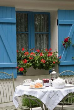 Dining Outdoors in the Garden Patio with Flowers in windowbox, house window and blue shutters, French feeling