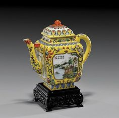 """Chinese Famille Rose Porcelain teapot  Delicately Famille Rose enameled, Chinese porcelain teapot and cover; square form with landscape and floral panels on engraved yellow enameled ground, seal mark; H: 7"""", fine hardwood stand Starting Bid: USD 250  I.M. Chait: Beverly Hills, CA, USA  Auction Date: January 13, 2013"""