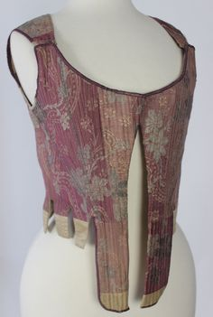 Stays, France, c. 1750. Plum silk with pink and metallic floral brocade, decorated with a narrow metallic braid, linen lining.