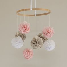 "A one of a kind baby mobile, handmade with baby pink, natural linen and white pom poms. The 9"" in diameter hoop has eight gorgeous hand stitched poms hanging from it at various heights. Hundreds of chiffon & natural linen petals make up the three pink, three natural and two white poms, ensuring each pom is lovely and full. The mobile is held together by a beautiful satin white ribbon and each pom is suspended from the hoop on a matching thread. Each pom is approximately 3 inches in diameter…"