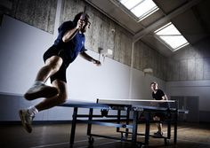 Table tennis in action. A player leaps into the air to hit a final smash. Part of a series of table tennis images shot for Sports Insight magazine by CliQQ Photography.