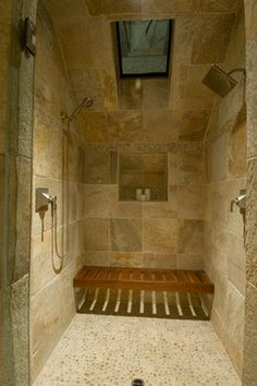 a spa like web room with double showers the teak seat is lovely the pebble floor tile leaves room for extra grout to reduce slips by dc fine homes