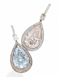 A pair of colored diamond ear pendants. Weighing approximately 7.18 and 8.04 carats.